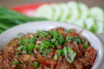 """""""Nam Prik Ong"""" one of famous Northern Thai food. It is made with ground pork, tomato and chili paste, fresh green onion and cilantro on the top and eat with rice and vegetable."""
