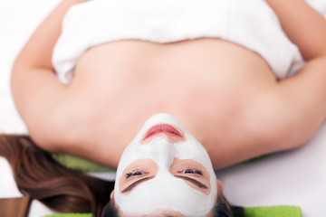 Spa concept. Hand applying nourishing mask on female face in spa salon
