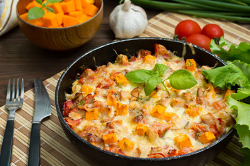 Casserole with chicken and pumpkin in a pan. Wooden rustic background. Close-up