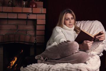 Портрет женщины у камина, которая читает книгу