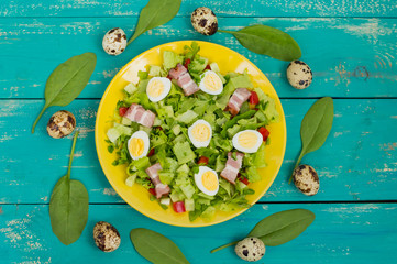 Salad with spinach, quail eggs and bacon. Wooden table. Top view