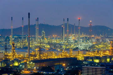 Oil refinery light nigh view with mountain background at twilight