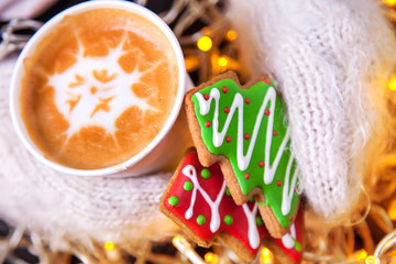 Coffee and Christmas cookies in hand mittens