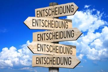 """Wooden signpost - """"Entscheidung"""" (German)/ """"Choice"""" (English)."""