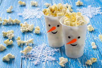 Plastic cups in the form of snowmen with popcorn. The idea for the Christmas party