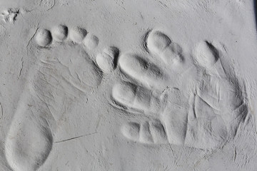 Tiny footprint and handprint texture on grey clay