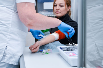 Preparation for blood test with pretty young blond woman by female doctor