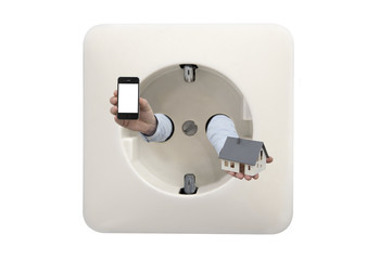 Close up on wall electrical outlet with mans hands holding smartphone and house model as concept for smart home app