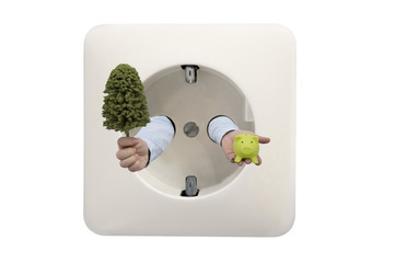 Close up of wall electrical socket with mans hand holding tree and green piggy bank in concept for green energy savings