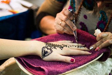 woman is performing tattoo with henna