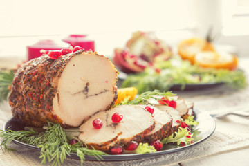 Christmas holiday dinner. Stuffed chicken breast with herbs, tomatoes, pomegranate and spices against holiday  background. Coloring and processing photo.