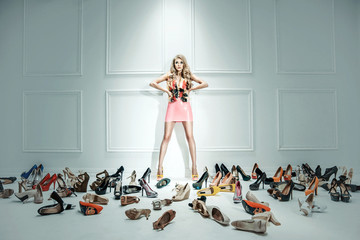 Conceptual image of a sensual lady with hundreds of shoes