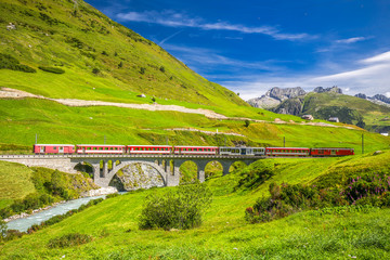 The Matterhorn - Gotthard - Bahn train on the viaduct bridge near Andermatt in Swiss Alps