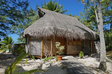 Wooden tropical bungalow with thatched roof on a motu of the atoll of Tikehau, Tuamotu, French Polynesia, south Pacific