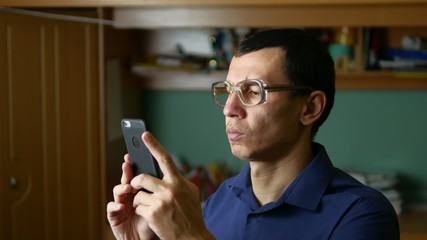 middle-aged man doing selfie photo with glasses and shirt indoor
