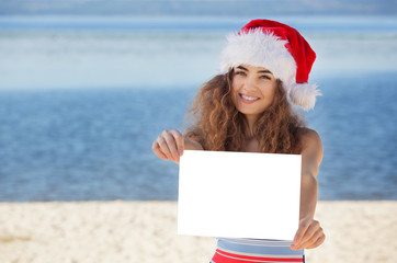 Young attractive curly girl in a bathing suit and hat of Santa Claus on the beach holding a white sheet of paper. The concept of the New Year and Christmas holidays.