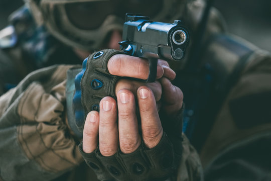 the soldier in the performance of tasks in camouflage and protective gloves holding a pistol with the hammer cocked takes aim for shot. War Zone.
