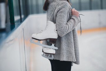 Woman at ice-skating rink holding skates.