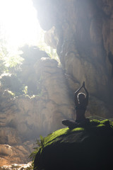 Fototapete - Silhouette of a young woman practicing yoga in the cave