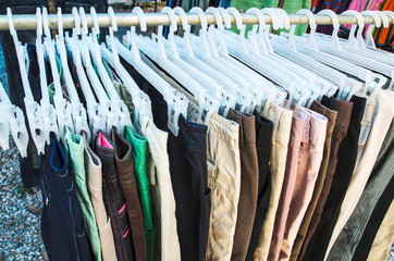 Row of pants and trousers on hangers for sale