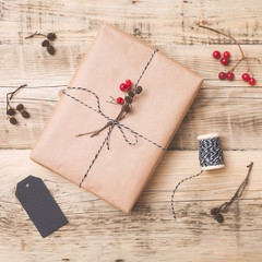 Top view on Christmas gift wrapped in craft and decorated with various natural things. DIY present idea. Holidays concept.