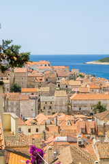 Overlooking a typical vista of the old town in Hvar Town, Croatia, with the orange terracotta rooftops and the azure Adriatic Sea.