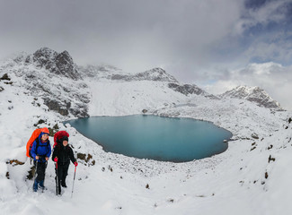 Two hikers feeling small standing in front of the huge blue mountain lake in winter snowy mountains