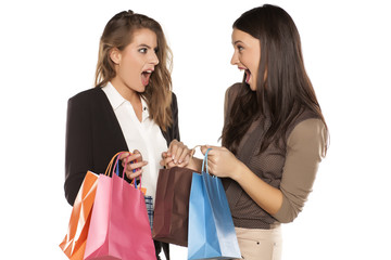Two girls with shopng bags brag to each other