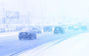 A lot of many cars on the highway in winter in the city in snowfall or blizzard, snow flakes falling, soft focus, light background toned blue. Concept slippery dangerous road.