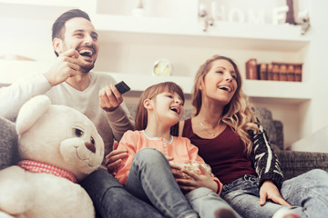 Happy family watching TV together at home