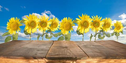 Obraz drewniany stół ze słonecznikami w tle - fototapety do salonu