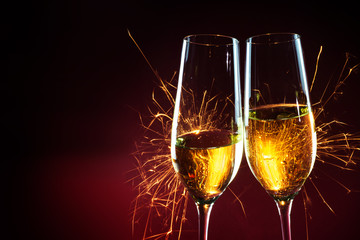 New Year party time with two champagne glasses and sparklers against a dark red background