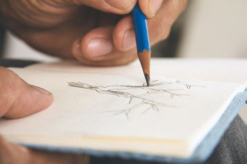 man writing a tree on sketchbook,Environment Conservative concept Wall mural