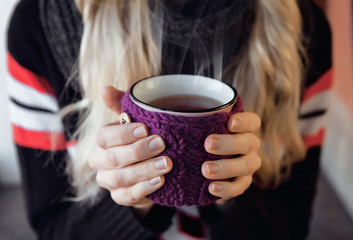 girl is in winter by snow and holding a mug of hot tea