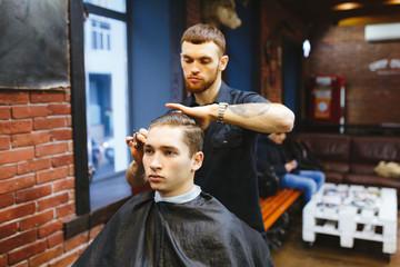 Master cuts hair of men in the barbershop