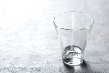 Empty glass on a grey wooden table