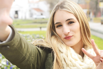 Portrait of young woman taking selfie.