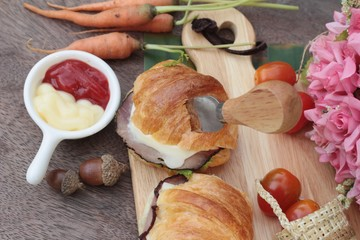 Croissant sandwich with grill pork, vegetable and cheese.