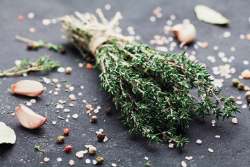 Herb thyme and spices on black kitchen table closeup.