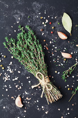 Food background of herb thyme and different spices on black kitchen table from above.