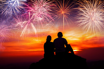 Happy couple sitting on floor and watching the fireworks