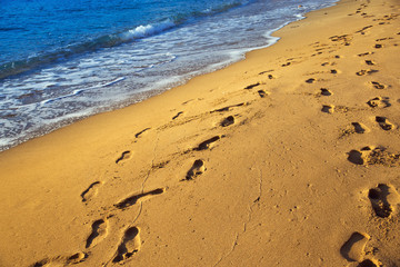 Sand beach. Scenic seacoast. Human footprints on the sand. Natural scenery