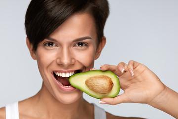 Nutrition. Beautiful Smiling Woman Biting Organic Green Avocado