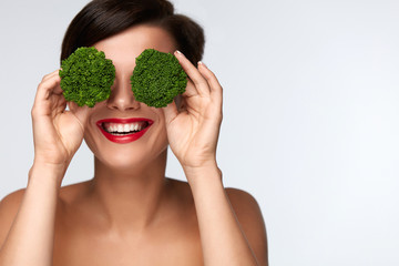 Food For Health. Beautiful Woman Holding Broccoli Before Eyes