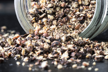 Coarsely ground black pepper spilling from a spice jar