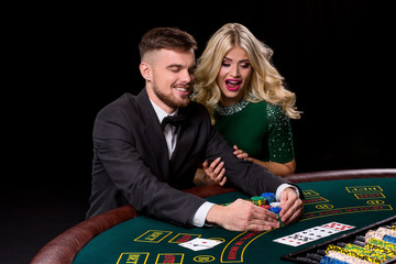 View of young, confident, man with the lady while he's playing poker game.