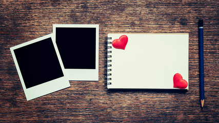 Blank photo frame, notebook, pencil and red heart on wood table