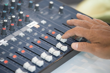 human finger addjust on audio mixing console