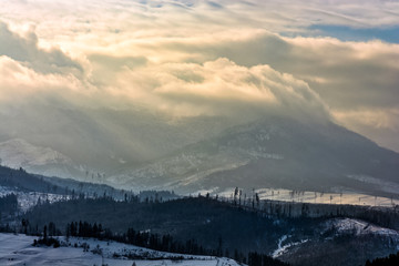 heavy clouds over mountains in snow