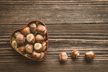 Hazelnuts in a heart shaped tin can on a wooden board background in vintage style